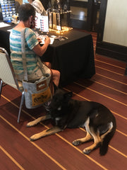 Kelly sitting trying out pens while a GSD named Bailey lies down beside.
