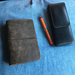 A leather notebook cover, a leather pen case, and a small orange vintage pen.