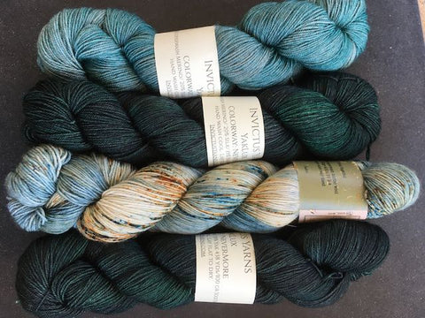 Four skeins of blue green yarn. Two dark and two light.