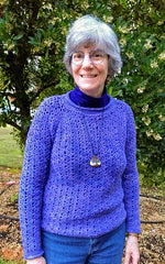 Amy smiling as she wears a periwinkle crocheted sweater