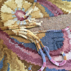 Rug with damage showing strips pulled off of the backing