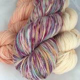 Pale peach and even paler apricot skeins along with a variegated purple and orange skein.