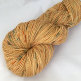 Pale orange yarn with dark orange and aquamarine speckles.