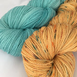 skein of aquamarine yarn with skein of orange yarn with aquamarine speckles