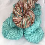two skeins of aquamarine yarn with a skein of variegated browns and teal