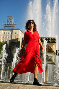 Red dress next to a fountain in Berlin, blowing in the wind.