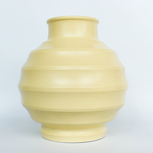 A Keith Murray design vase for wedgewood , sometimes known as football vase with deep horizontal ribs in a cream glaze. Full signature underneath at Jeroen Markies.