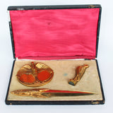 A gilt bronze and onyx in a bird motif, including letter opener and inkwell tray. In fitted presentation case. All signed,