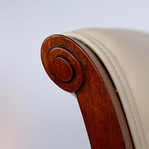A pair of side chairs with walnut frames. Scrolled and carved detail to frames. Upholstered in cream leather.