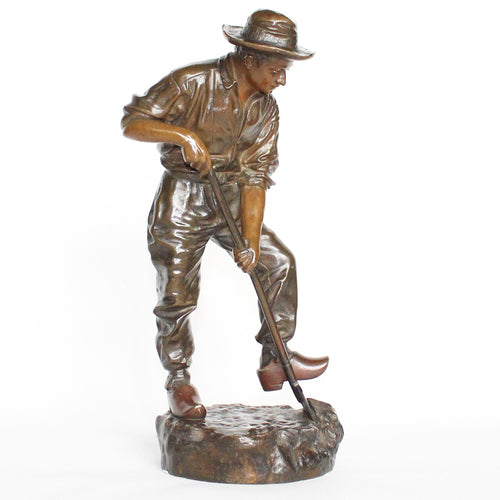 A patinated bronze field worker digging the soil. Set over an integral, naturalistic plinth. Signed J Garnier to base at Jeroen Markies