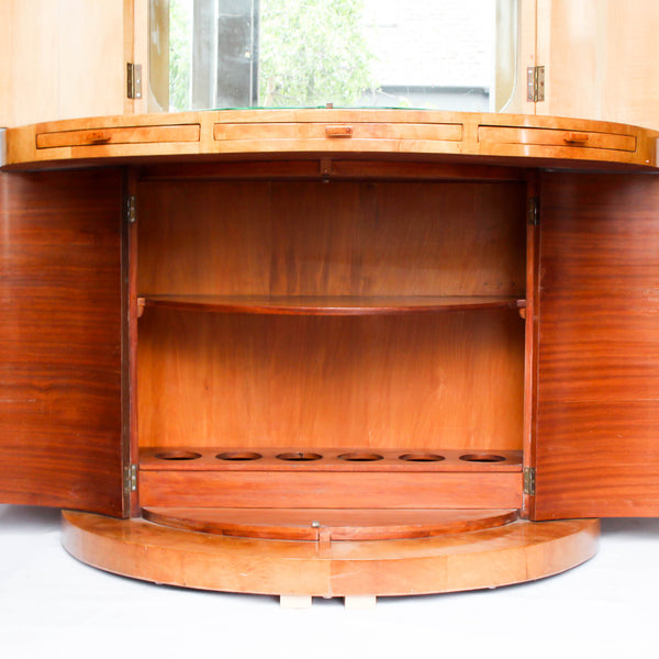 An Art Deco, demi-lune cocktail cabinet attributed to Harry & Lou Epstein. Mirrored, lit interior to top with glass shelves and mirrored slide tray. Lower, shelved cabinet with bottle holders. Burr walnut veneer at Jeroen Markies.