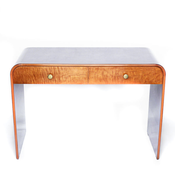An Art Deco, two drawer desk in satin wood veneer with oak and satin birch drawer linings. Original brass handles.