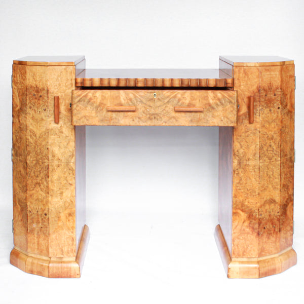 An Art Deco console sideboard by Hille. Burr walnut veneer throughout. Scallop-edged detail to front with integral drawer. Shelved cabinets to either side.