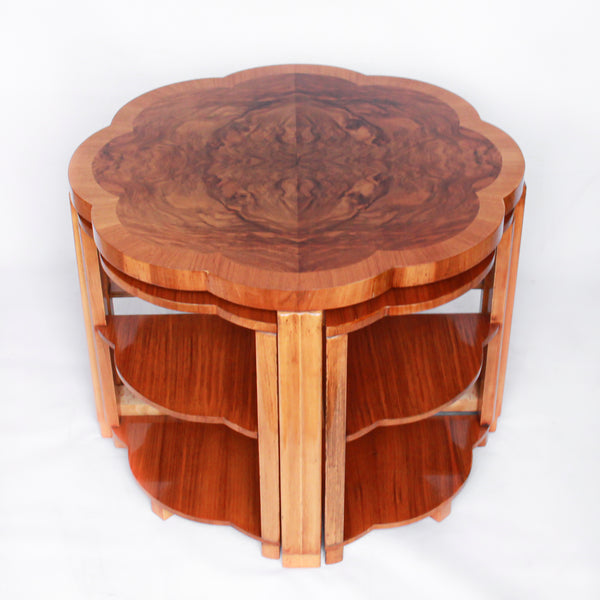 An Art Deco nest of tables in figured and straight grain walnut veneer. Main table with shaped edging set over cross footed base. Four shelved, integral side tables.