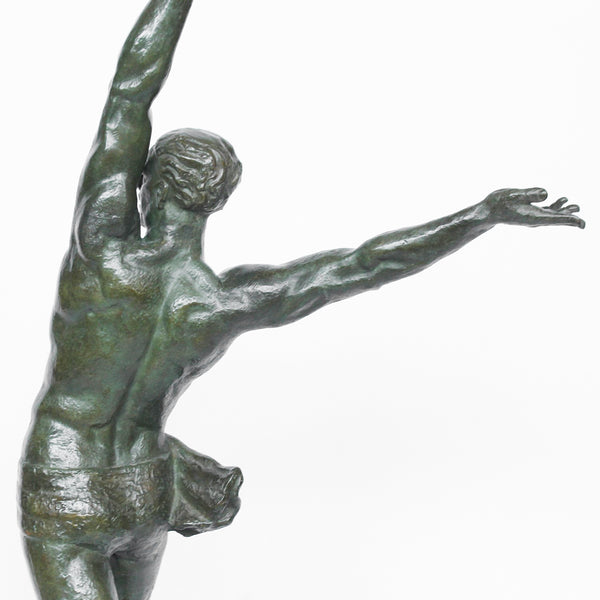 An art deco verdigris patinated bronze sculpture of an athletic young man on a rocky plinth holding a victor's laurel wreath at Jeroen Markies
