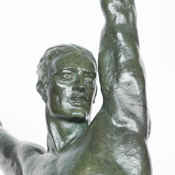 'Olympian', an Art Deco verdigris patinated bronze figure . An athletic young man standing on a rocky plinth holding a victor's laurel wreath aloft. Signed 'PLE Faguays' and applied with a metal plaque inscribed 'Exposition Philatelique Nationale Grenoble 1934' at Jeroen Markies