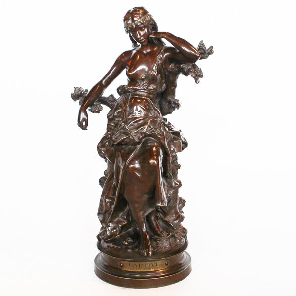 Captive, an Art Nouveau rich brown patinated bronze figure of a scantily clad young lady. Signed Hip Moreau to cast, and with title plaque to front at Jeroen Markies