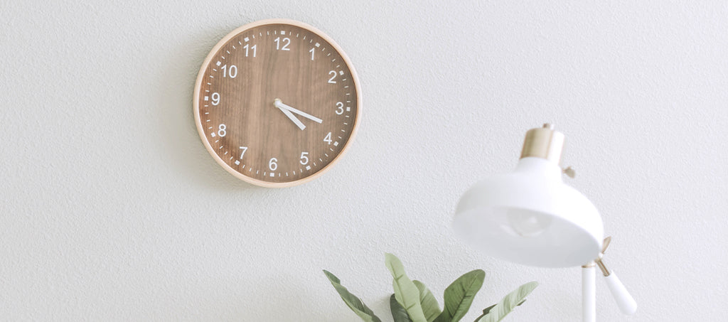 A wall clock with a wooden design