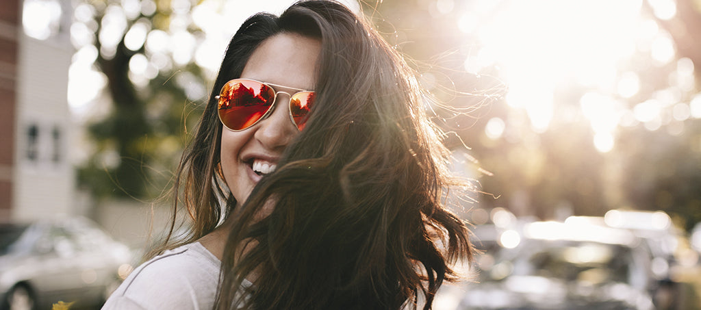 A young woman in sunglasses laughs