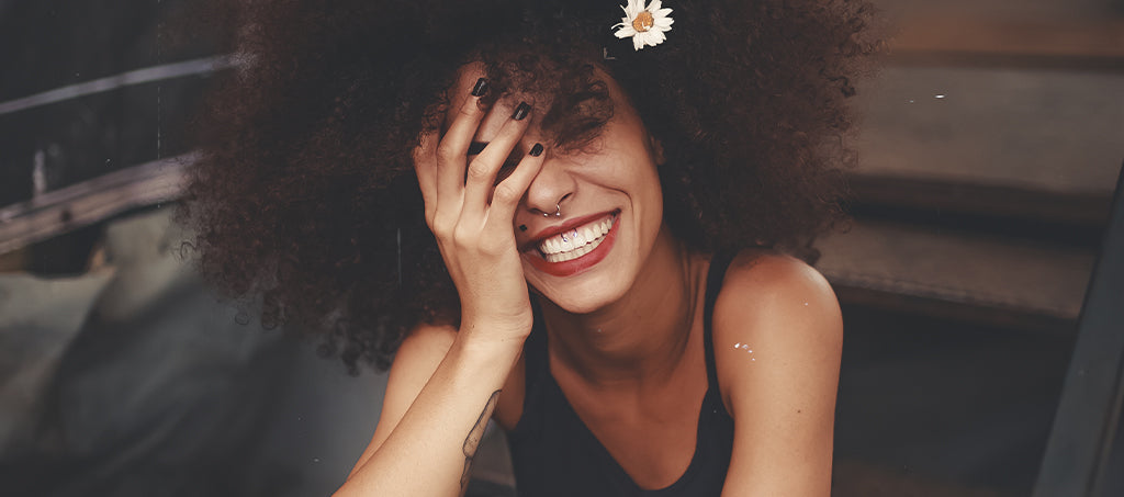 Woman with afro and piercings laughs