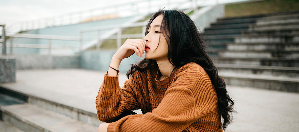 young asian woman is sitting outside on the stairs and is thoughtful