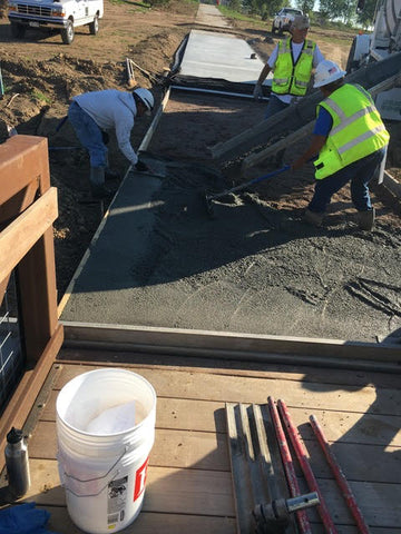 """Concrete workers installing the AGT 1/2"""" ULTRA Glow Stones into the fresh concrete surface."""