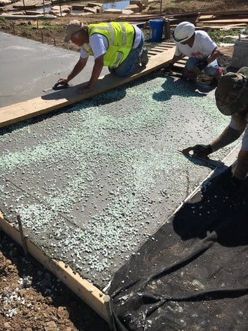 """Installing the AGT ULTRA Grade 1/2"""" Glow Stone into the fresh concrete surface."""