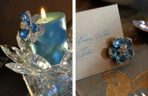 Aquamarine brooches are placed on a pillar candle and a wedding escort card.