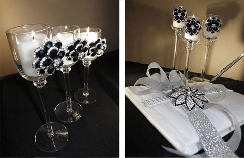 Black and silver brooches are used to accent candle holders and a wedding guest book.