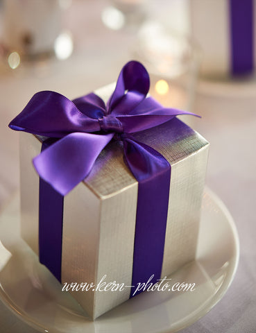 A guest gift wrapped with satin ribbons and bows sitting on a side plate.