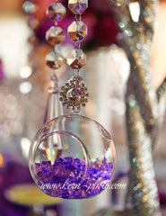 A clear bubble candle holder with purple nuggets and votive candle.