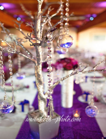 A faux tree decorated with hanging crystals and bubble votive candle holders.
