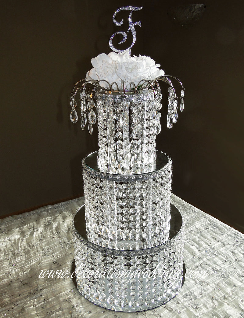 Three stacked crystal tiers and a graceful arch topper with a Swarovski monogram.
