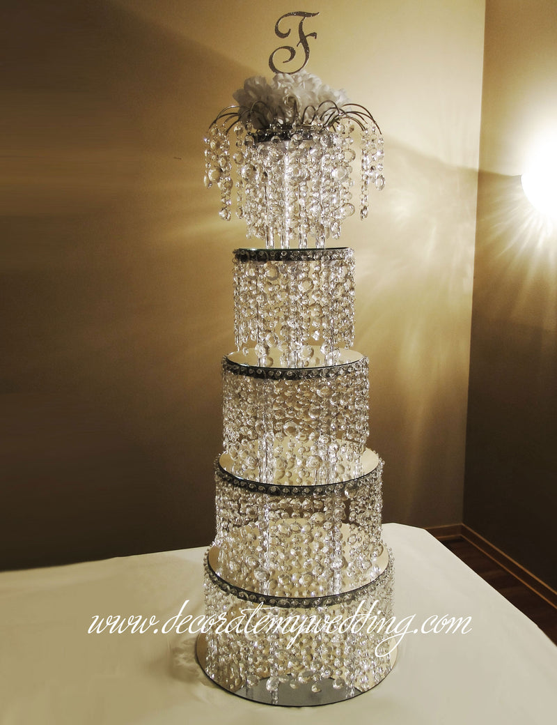 Five crystal bead tiers are stacked one on top of the other, and topped with a matching arch topper and a Swarovski monogram.
