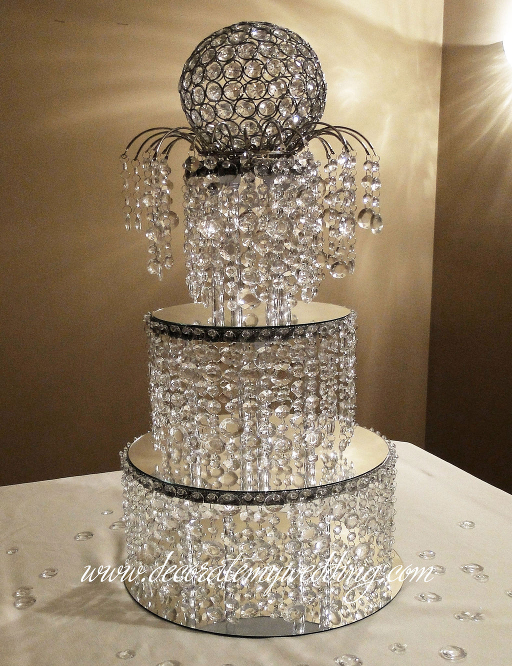 Three stacked crystal tiers are topped with a matching arch topper and a beaded globe.