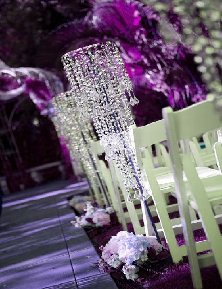 Church aisle decorations are created using multi-cut diamond hanging chandeliers.
