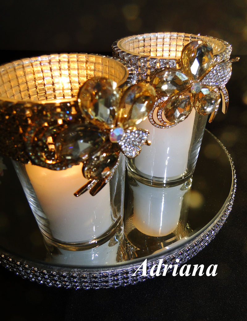 Two votive holders accented with amber brooches.