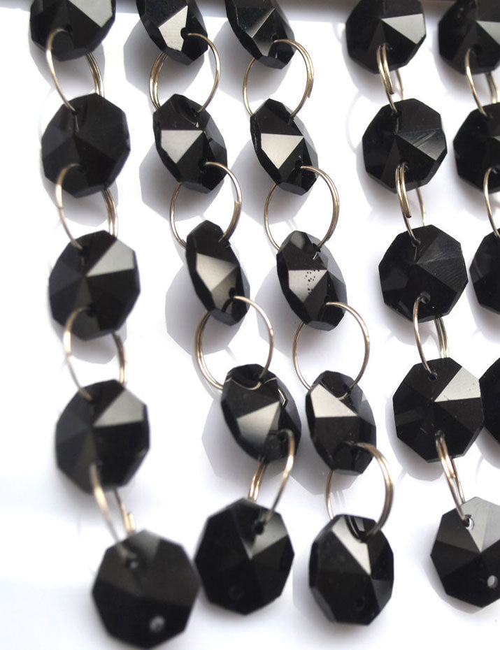 Black beads are connected with silver rings to create a long garland strand.