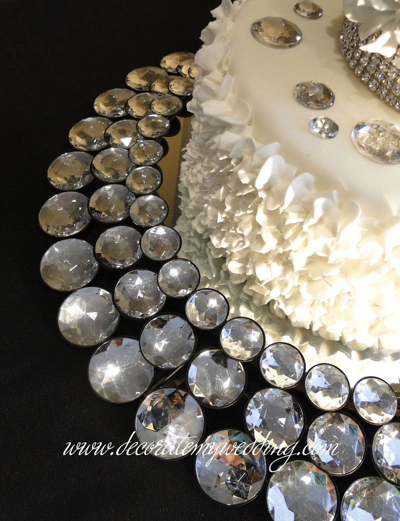 This bling cake stand consists of three rows of multi-size rhinestones that circle a small wedding cake.