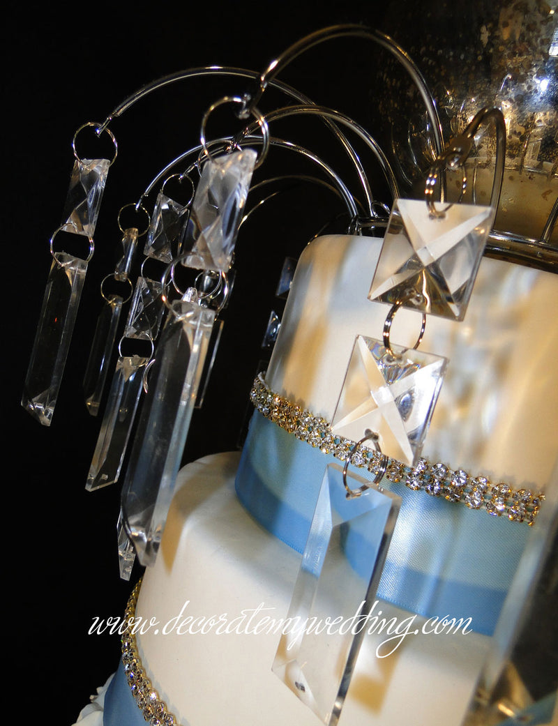 This bling cake topper has multi-size square and rectangular crystal prisms that hang from a metal arch.