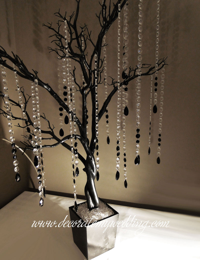 A full view of a wedding tree with hanging black teardrops.