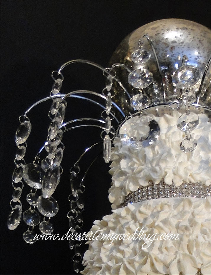 Sparkling circle beads dangle off this crystal top decoration to make a stunning cake topper.