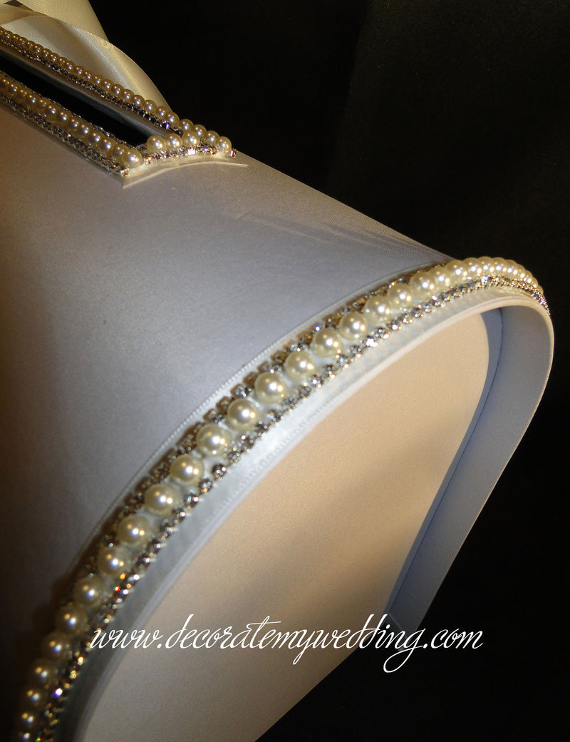 A close up look at the white satin fabric, and the pearl trim on the curvature of the box.