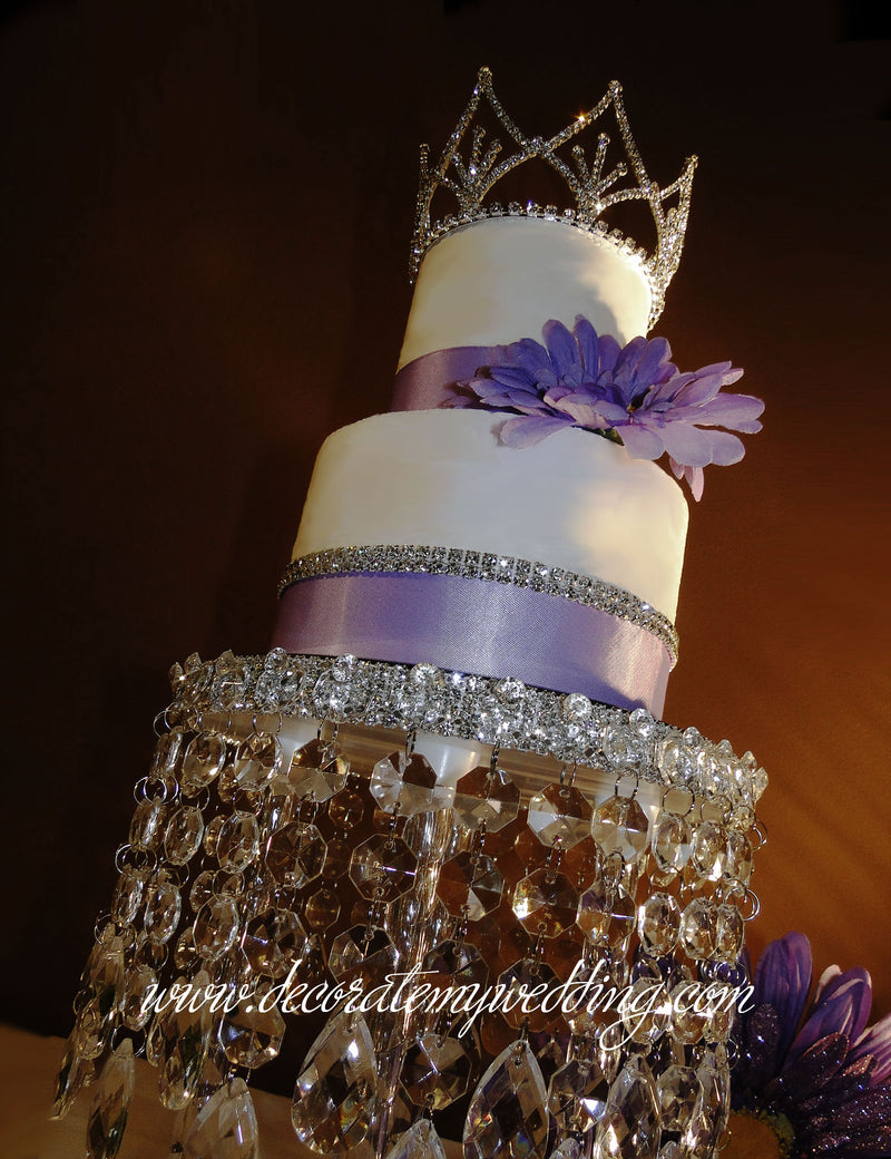 Full view of crown decoration sitting on top of a wedding cake.