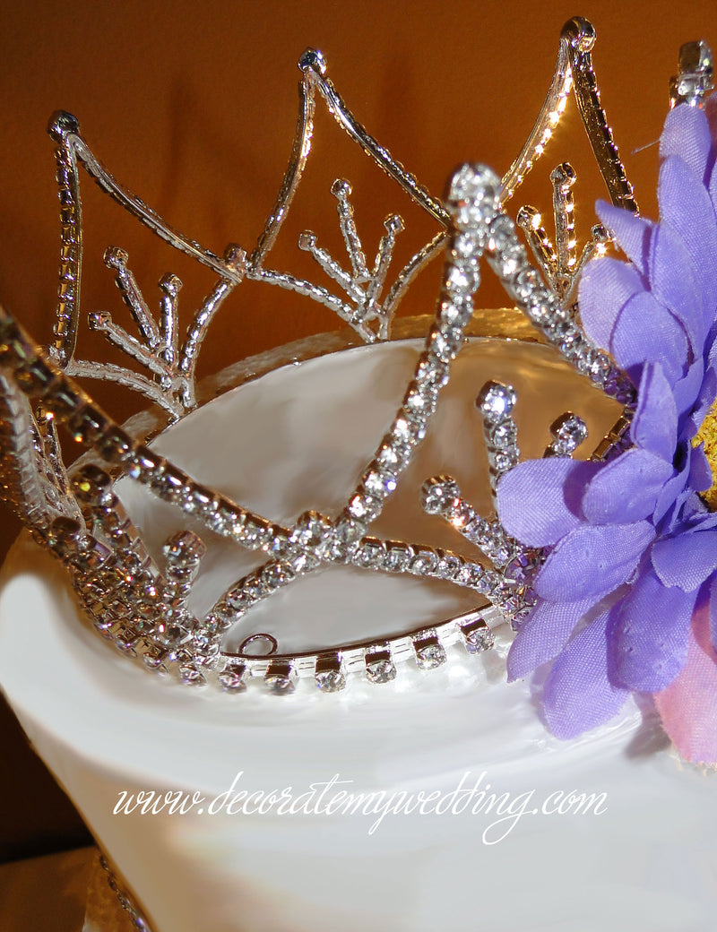 A close up look at the crown decoration sitting on the top layer of a wedding cake.