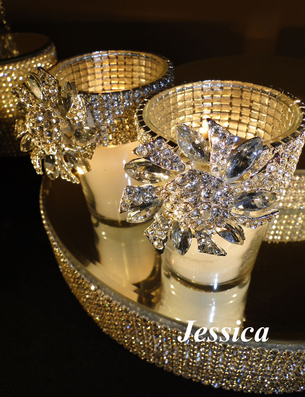 Two votive holders sit on a mirrored platform decorated with clear brooches.