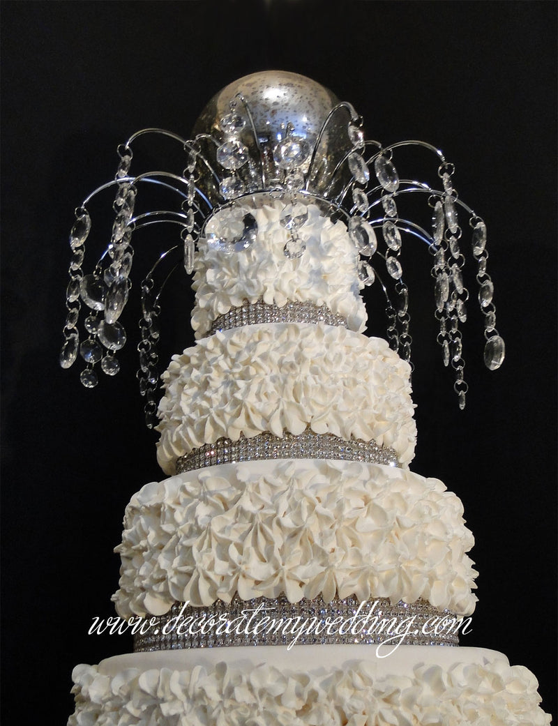 A full view of the cake top decoration sitting on the top of a wedding cake.