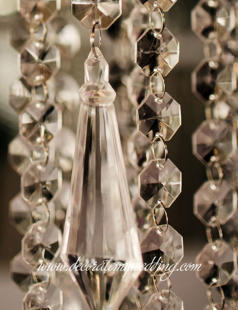 A full view of the large diamond bead pendant hanging among clear octagon bead strands.