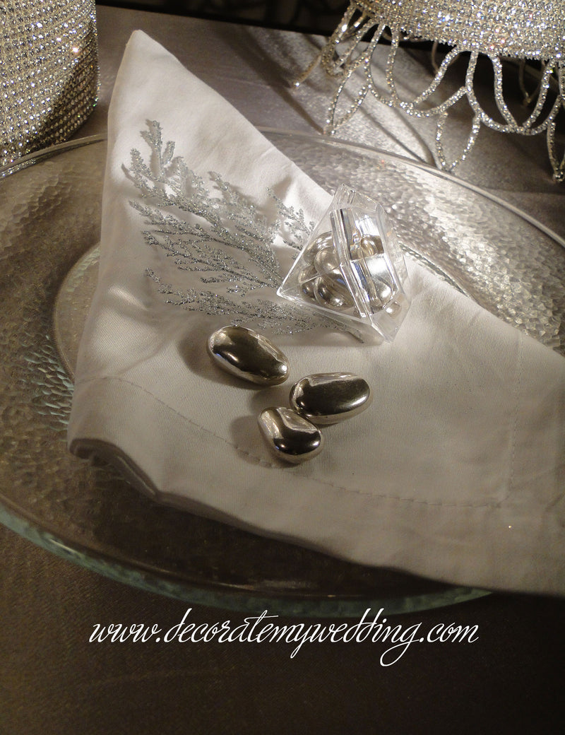 Diamond favor container filled with metallic silver Jordan almonds placed on a napkin at each table setting.