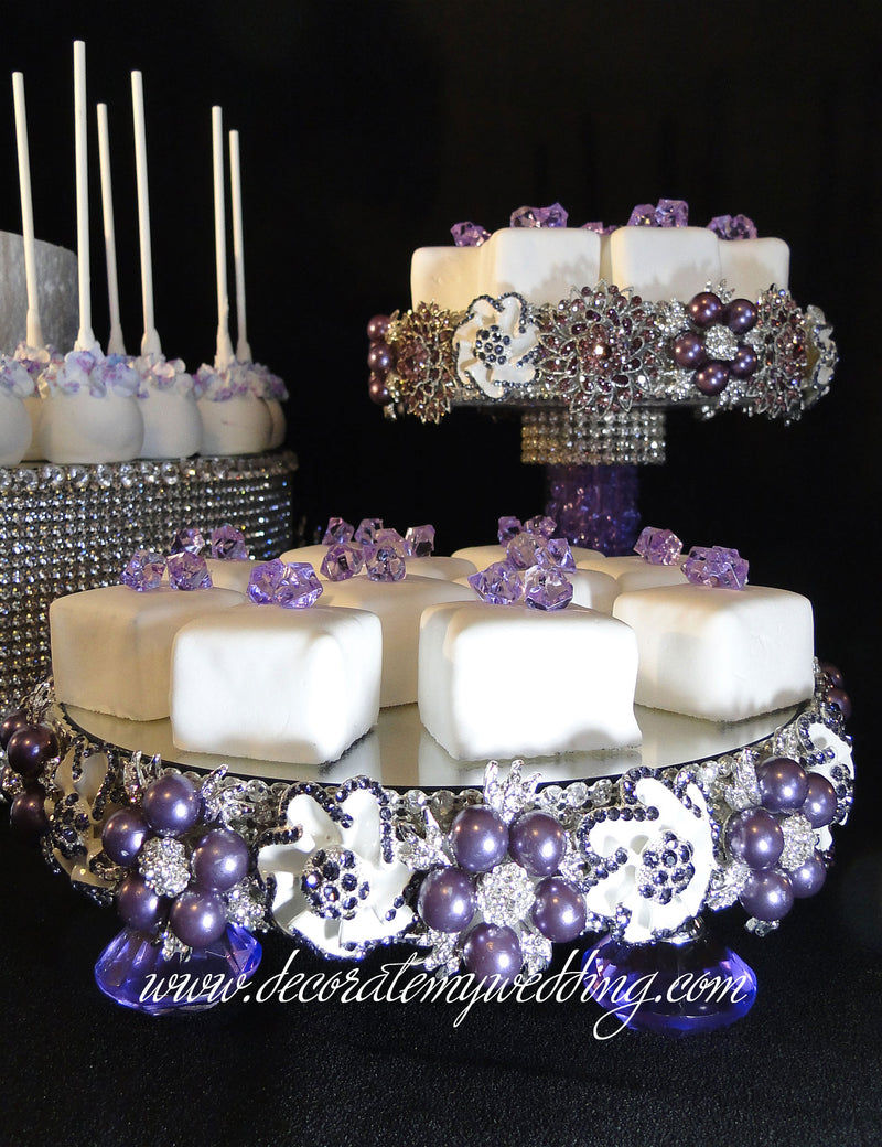 This stunning buffet stand is surrounded by gorgeous purple rhinestone brooches and matching crystal glass feet.
